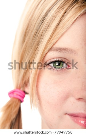 Beautiful green watchful eye of a teenage girl with blond hair pigtail, isolated.