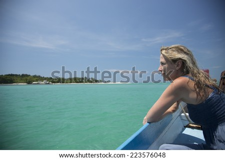 Beautiful green water, blue sky, ocean and island with blonde woman