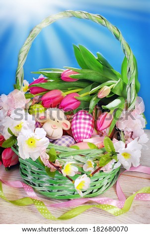 beautiful green wicker basket with eggs,sheep and tulips on blue background