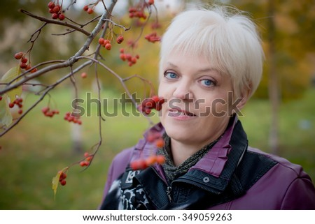 Beautiful grey senior woman relaxing in the fall park