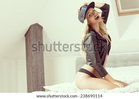 Beautiful gril with long, blonde, curly hair is on the bed. She is wearing black underwear, leather jacket andd fullcap. She has got purple lips. - stock photo