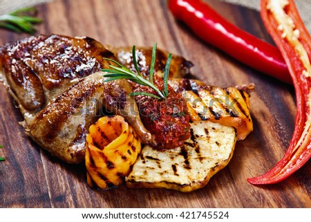 beautiful grilled quail with grilled vegetables and rosemary on a wooden Board in the restaurant - stock photo