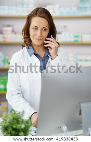 Beautiful grinning middle aged female pharmacist taking orders on phone from behind desk with large monitor in front of her