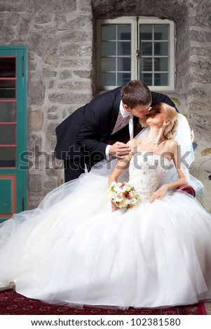 beautiful groom and bride kissing in interior on wedding day - stock photo