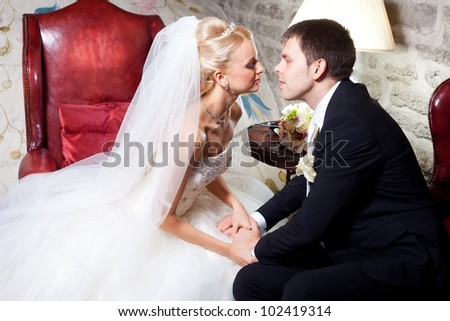 beautiful groom and bride sitting in interior on wedding day - stock photo