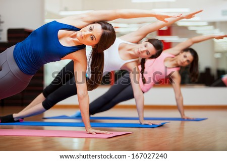 Beautiful group of women practicing the side plank yoga pose during a class in a gym - stock photo