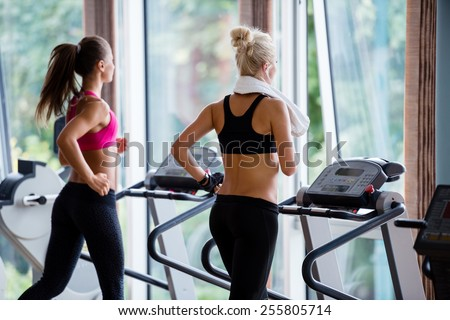 Beautiful group of young women friends  exercising on a treadmill at the bright modern gym - stock photo