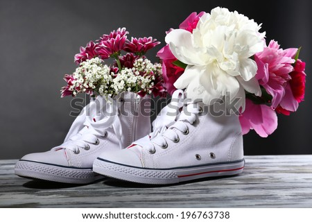 Beautiful gumshoes with flowers inside, isolated on white - stock photo