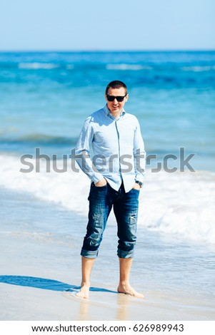 Beautiful  guy with a camera on the beach