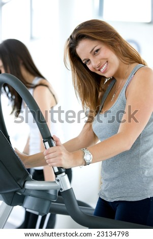 Beautiful gym woman exercising on a cardio machine smiling