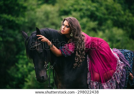 Beautiful gypsy in violet dress with a black horse