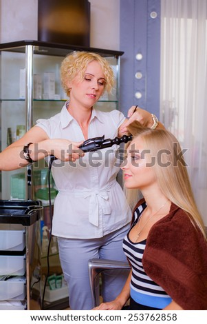 Beautiful  hairdresser giving a new haircut to female customer at parlor - stock photo