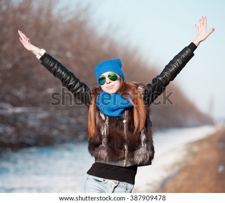 Beautiful haired sexy woman, dressed blue jeans, hat and scarf, fur jacket, sunglasses. Has long hair and elegant slim body, walking to road, go in hitch-hiking. Portrait urban city. Real lady. - stock photo