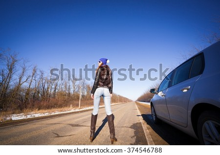 Beautiful haired sexy woman, dressed blue jeans, leather boots, fur jacket, sunglasses. Has long hair, legs and elegant slim body, stand to road near car. Portrait urban city. Real lady driver.  - stock photo
