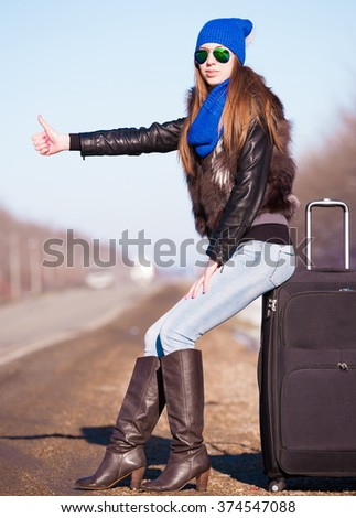 Beautiful haired sexy woman, dressed blue jeans, leather boots, fur jacket, sunglasses. Has long hair, legs and elegant slim body, walking to road and holding suitcase. Portrait urban city. Real lady. - stock photo
