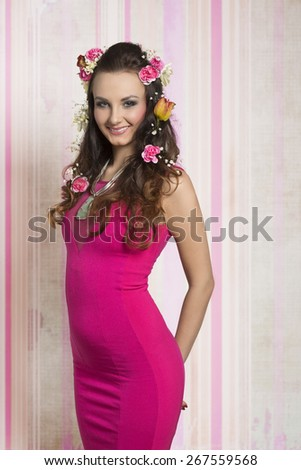 Beautiful, hairy, natural, stunning woman with curly brown hairstyle with spring flowers. She is wearing pink sexy dress and nice big necklace. - stock photo