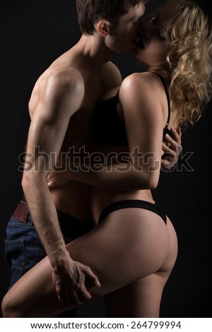 Beautiful half naked couple kissing, about to have sex, passionate foreplay in the darkness, studio low key shot, black background
