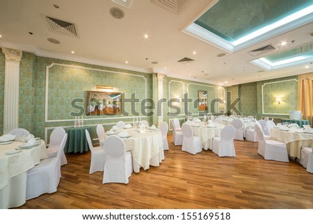 Beautiful hall with pictures and tables in a restaurant decorated for a wedding celebration,  in place of pictures photo by the author. - stock photo