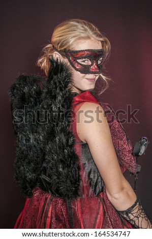 beautiful Halloween black angel isolated on dark red  background