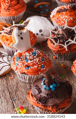 Beautiful Halloween cupcakes with ghosts and witch hat close-up on the table. vertical