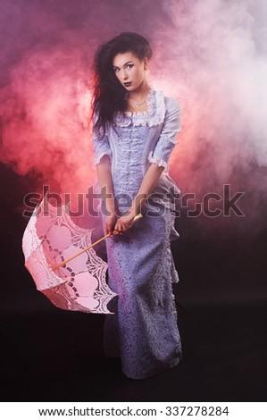 Beautiful Halloween vampire woman aristocrat with lace-parasol - stock photo