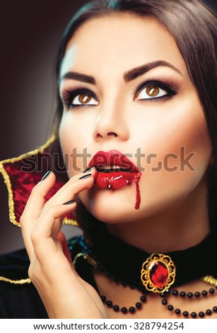 Beautiful Halloween Vampire Woman portrait. Beauty Sexy Vampire lady with blood on her mouth. Fashion Art design. Attractive model girl in Halloween costume and make up  - stock photo