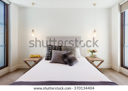 Beautiful hamptons style bedroom decor in luxury home interior with pendant lighting - stock photo