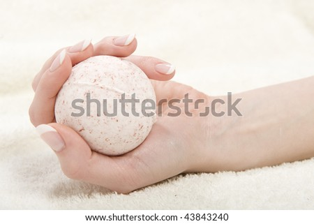 Beautiful hand with perfect french manicure and strong nails holding round soap - stock photo