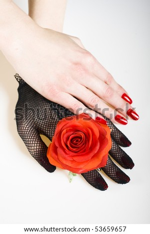 Beautiful hand with perfect nail red manicure, rose and black retro glove