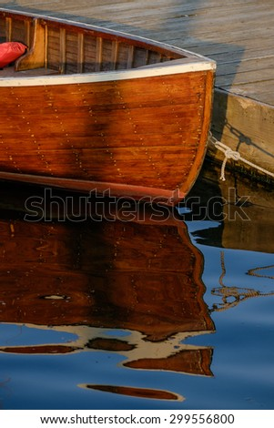 Beautiful handcrafted rowboat bow and reflection at sunset in a calm harbor - stock photo