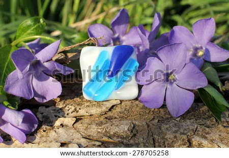 beautiful Handmade glass ring with wood violet in spring on the nature background - stock photo
