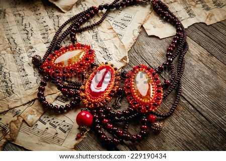 Beautiful handmade necklace on wooden background - stock photo