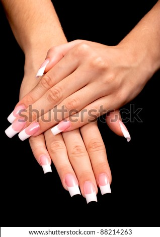 Beautiful hands with french manicure on black background - stock photo