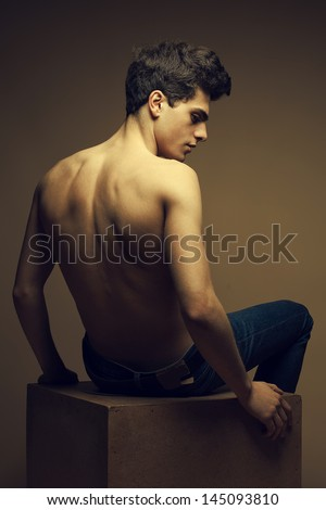 Beautiful (handsome) muscular male model in blue jeans with perfect muscular body posing over wooden background, sitting on a wooden cube. Vogue style. Fashion studio portrait