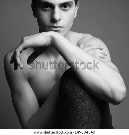 Beautiful (handsome) muscular male model in jeans (denim) sitting and posing over gray background. Healthy skin. Vogue style. Black and white (monochrome) fashion studio portrait