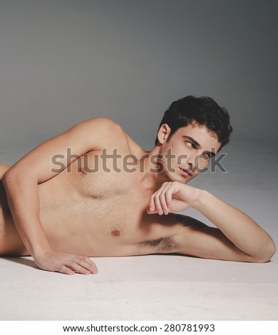 Beautiful (handsome) muscular male model lying down in studio
