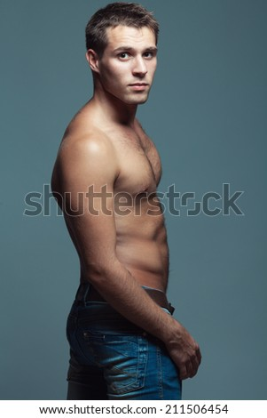 Beautiful (handsome) muscular male model with nice abs in blue jeans with leather belt posing over blue (gray) background. Urban style. Fashion studio portrait - stock photo