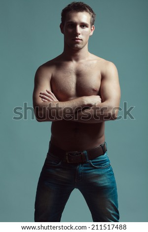 Beautiful (handsome) muscular male model with nice abs in blue jeans with leather belt posing over blue (gray) background. Hands crossed. Urban style. Fashion studio portrait - stock photo