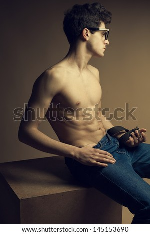 Beautiful (handsome) muscular male model with nice abs in jeans posing in trendy glasses. Boy sitting on a wooden cube. Hipster style. Copy-space. Fashion studio portrait - stock photo