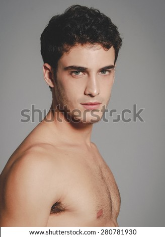 Beautiful (handsome) muscular male model with nice body posing over light-gray background.