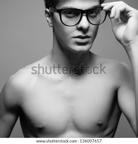 Beautiful (handsome) muscular male model with nice body wearing trendy glasses and posing over light-gray background. Hipster style. Close up. Black and white (monochrome) studio portrait.