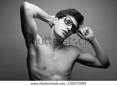 Beautiful (handsome) muscular male model with nice body wearing trendy glasses and posing over light-gray background with hands up. Hipster style. Black and white (monochrome) studio portrait. - stock photo