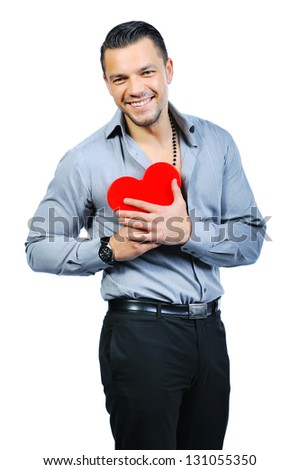 Beautiful handsome young macho man holding love heart and smiling to you - stock photo