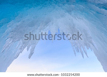 Beautiful hanging icicles in ice cave against blue sky.