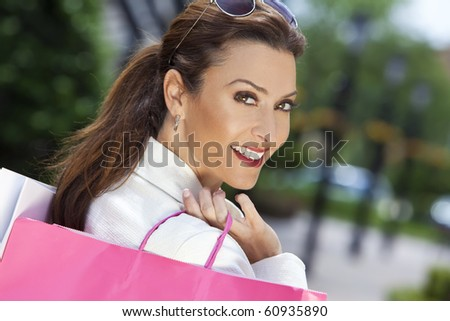 Beautiful, happy and fashionable woman with colorful pink and white shopping bags - stock photo