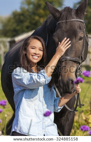 Beautiful happy Asian Eurasian young woman or girl wearing denim shirt, smiling and leading her horse in sunshine - stock photo