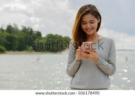 Beautiful happy Asian woman outdoors using mobile phone