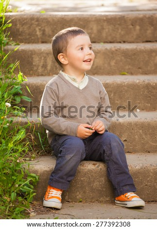 beautiful happy baby boy sitting on the old steps, outdoors shoot - stock photo