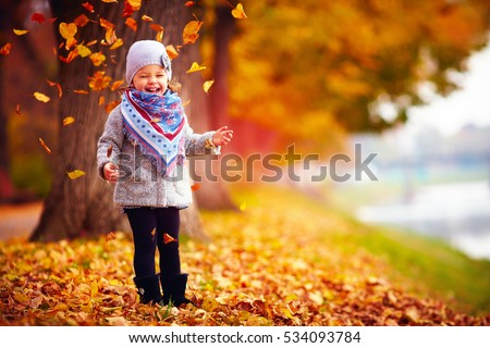 beautiful happy baby girl having fun in autumn park, among fallen leaves