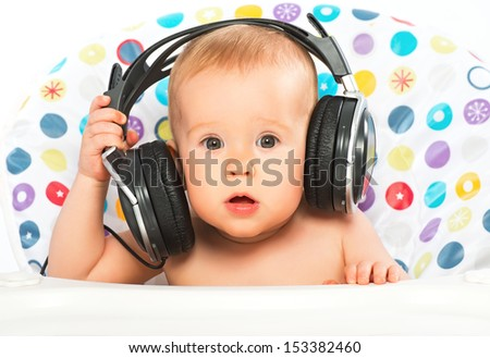 beautiful happy baby with headphones listening to music - stock photo